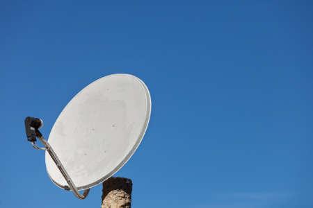 Biała antena satelitarna na tle błękitnego nieba. Antena telewizyjna na dachu domu. Koncepcja sprzętu cyfrowego technologii bezprzewodowej.