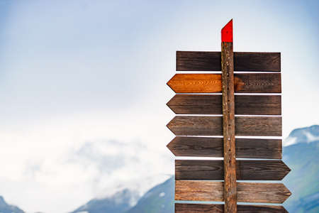 Tourism vacation and travel. Wooden signpost in norwegian mountains. Rainy cloudy weather. Zdjęcie Seryjne