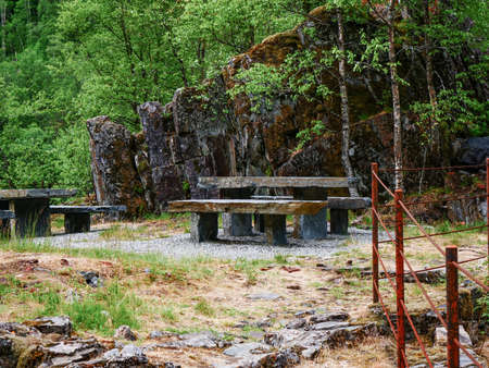 Picnic site stone table with benches on nature at path in Allmannajuvet area Sauda, Norway. Norwegian national tourist scenic route Ryfylke.