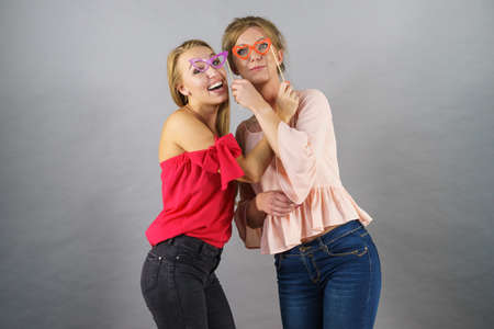 Happy two women holding paper decoration photo booth mask glasses on stick, having fun. Wedding, birthday and carnival funny accessories concept. Foto de archivo - 134598796