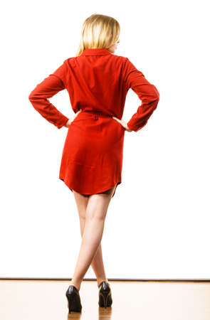 Super fashionale woman wearing elegant casual red short dress and black stylish high heels.