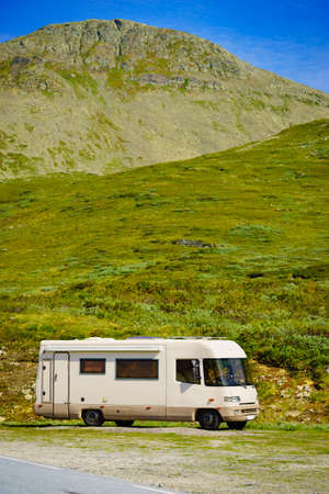 Tourism vacation and travel. Camper car in green summer mountains landscape. National tourist route Aurlandsfjellet. Zdjęcie Seryjne