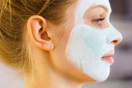 Woman with green mud mask on face, side view. Teen girl taking care of oily skin, purifying the pores. Beauty treatment. Skincare. Stock Photo