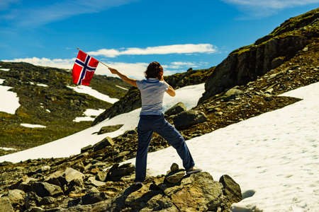 Tourist woman holding norwegian flag and taking photo with camera, snowy mountains landscape, summertime. National tourist route Aurlandsfjellet.