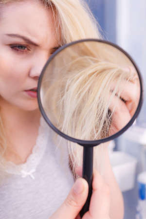 Haircare, bad effects of bleaching concept. Unhappy woman looking at ends of her blonde hair through magnifying glass