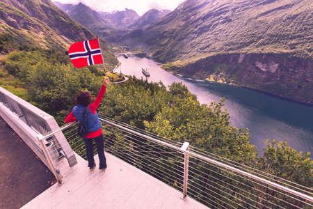 Female tourist with norwegian flag enjoying scenic view over fjord Geirangerfjord with cruise ship. Cruising vacation and travel.