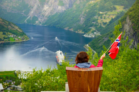 Female tourist enjoying scenic view over fjord Geirangerfjorden from Flydalsjuvet viewpoint, holding norwegian flag. Cruising vacation and travel.