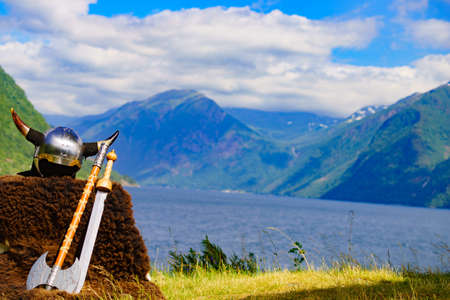 Viking helmet with weapons on fjord shore in Norway. Tourism and traveling concept Zdjęcie Seryjne