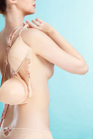 Bosom concept. Slim attractive naked woman holding beige plunge bra in hand, on blue Stok Fotoğraf