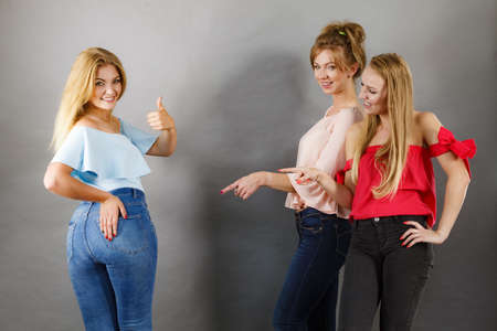 Woman wearing tight jeans showing off her curvy butt and female friends pointing at her.