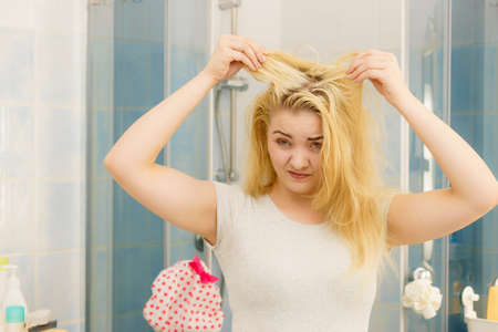 Blonde woman having problems with greasy oily hair looking at herself in bathroom. Female showing scalp, scratching herself, dandruff problem. 写真素材