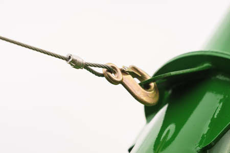 Metal rope hooked with a steel hook on structure object agricutural machine on white. Stock Photo
