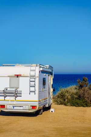 Camper, recreational vehicle on sea coast in Spain. Camping on nature beach. Holidays and traveling in motor home.