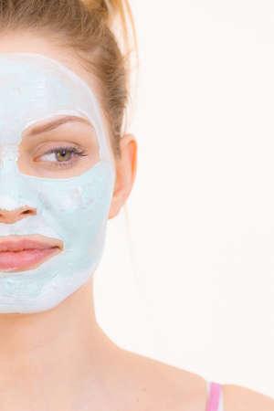 Jonge vrouw met groen moddermasker op gezicht, op wit. Tienermeisje dat de vette huid verzorgt, de poriën zuivert. Schoonheidsbehandeling. Huidsverzorging.