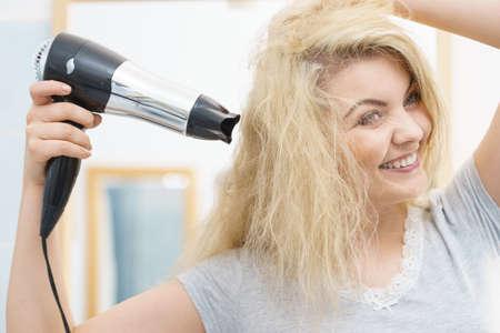Femme positive à l'aide d'un sèche-cheveux sur sa coiffure blonde. Soins capillaires, concept de coiffure.