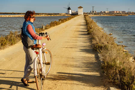 Mature woman with bicycle relaxing at San Pedro del Pinatar park, Murcia Spain. Tourist attraction. Activity on holidays