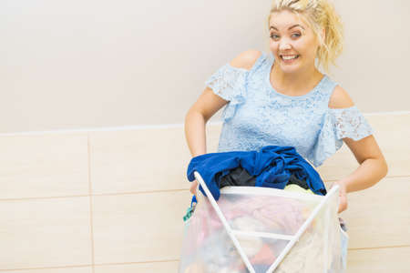 Happy cheerful woman holding big laundry basket full of colorful dirty clothes. Bathroom utensils concept. Stock Photo