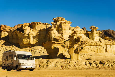 BOLNUEVO, SPAIN - MARCH 15, 2019: Camper Mobilvetta on parking area at eroded yellow sandstone formations, Enchanted City of Bolnuevo, Murcia Spain. Tourist attraction.