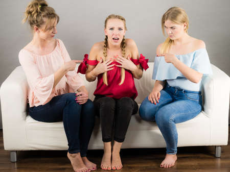 Woman being bullied by her two female friends. Females pointing blaming at friend. Friendship rivaly and envy problems.