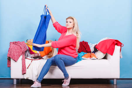 Style dilemmas concept. Woman does not know what to wear sitting on messy couch with piles of clothes and looking through clothing. Stock Photo