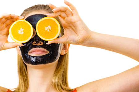 Woman with carbo detox black peel-off mask on face holding orange fruit. Teen girl taking care of oily skin, cleaning the pores. Beauty treatment. Skincare. 스톡 콘텐츠