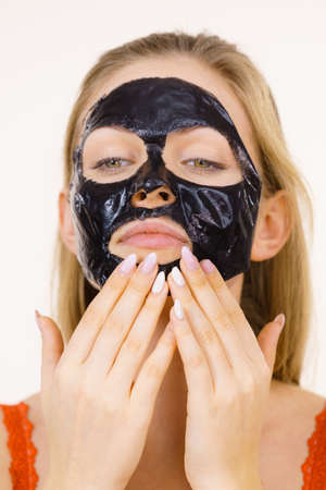 Young woman with carbo black peel-off mask on her face, cosmetic ready to remove, on white. Teen girl taking care of oily skin. Beauty treatment. Skincare.