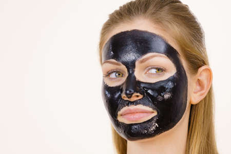 Young woman with carbo detox black peel-off mask on her face, on white. Teen girl taking care of oily skin, cleaning the pores. Beauty treatment. Skincare.