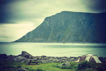 Tent on seashore in summer, cloudy hazy weather. Camping on ocean shore. Skagsanden Beach Flakstadoy Lofoten Norway. Holidays travel and adventure.
