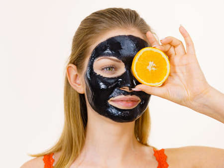 Woman with carbo detox black peel-off mask on face holding orange fruit. Teen girl taking care of oily skin, cleaning the pores. Beauty treatment. Skincare. Stock Photo
