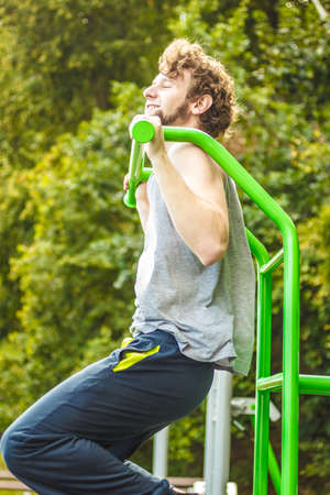 Active young man exercising on ladder. Muscular sporty guy in training suit working out at outdoor gym. Sport fitness and healthy lifestyle concept.