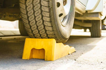 Camper leveling yellow block in use. Leveler ramp chock blocks for rv travel trailer. Accessories for motorhome.