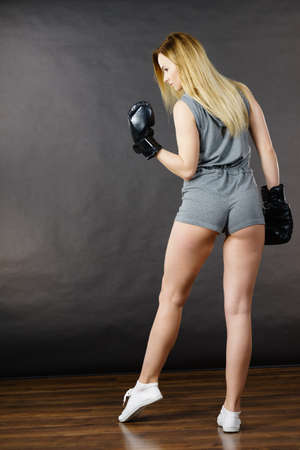 Sportsmanship fairplay and strong body. Young slim woman fighting boxing. Blonde girl wearing black punch gloves posing in full length. Sport and fitness, power, exercising. Back view Stock Photo