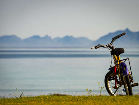 Child bike with safety helmet parked on beach seashore in summer. Lofoten archipelago Norway. Holidays and adventure. Banco de Imagens