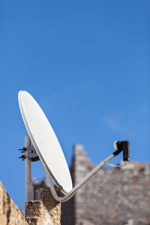 White satellite dish with background of blue sky. Tv antenna on home roof. Wireless technology digital equipment concept.