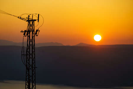 Coast with electricity transmission pylons, power lines high voltage towers. Sunset landscape in Spain