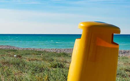 Seaside landscape. Spanish sea shore with yellow garbage bin or trash can. Keeping the beach clean. Standard-Bild