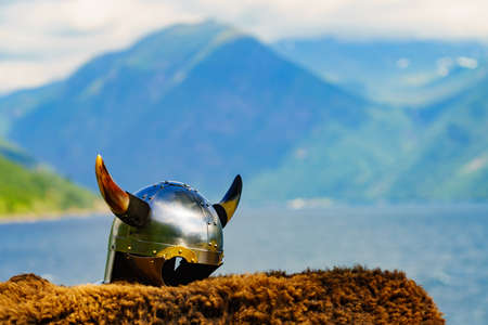 Viking helmet with sword on fjord shore in Norway. Tourism and traveling concept Stock Photo