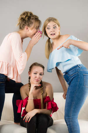 Woman being bullied by two female friends gossiping about her. Friendship rivaly and envy problems. Stock Photo