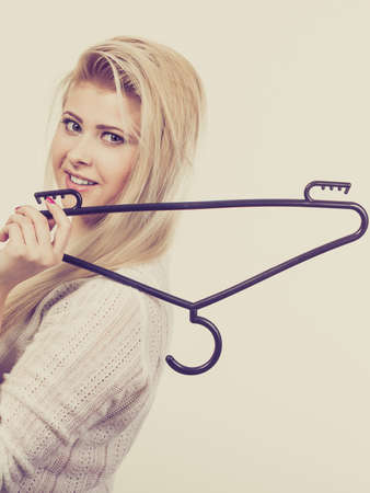 Doing cleaning in closet, wardrobe concept. Blonde woman holding black clothes hanger.