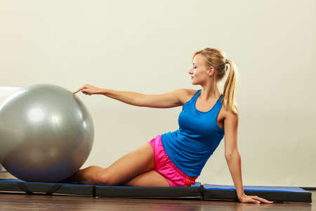 Sport, training, gym and lifestyle concept. Young attractive slim woman in sportswear doing fitness exercises with fit ball at home Stockfoto