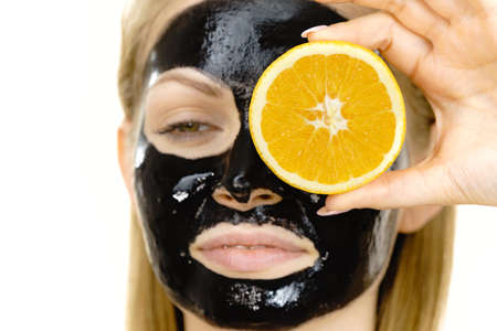 Woman with carbo detox black peel-off mask on face holding orange fruit. Teen girl taking care of oily skin, cleaning the pores. Beauty treatment. Skincare. Banque d'images