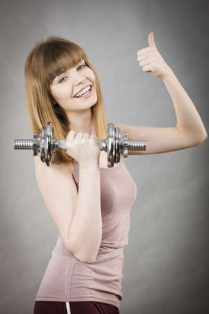 Young woman working out at home with heavy dumbbells. Training at home, being fit and healthy.