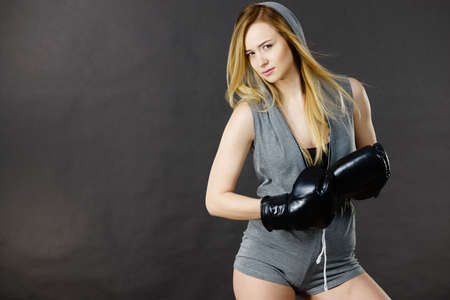 Young hooded woman fighting boxing. Blonde attractive girl wearing black punch gloves. Sport and fitness, power, exercising, on gray