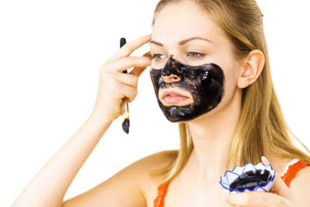 Young woman being apply with brush black detox mud mask to her face. Girl taking care of skin. Beauty treatment. Skincare.