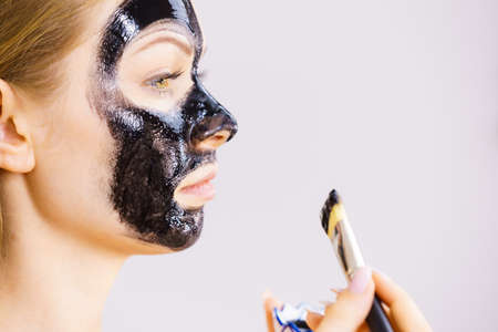 Young woman applying with brush black detox mud mask to her face. Girl taking care of skin. Spa treatment. Skincare. Side view