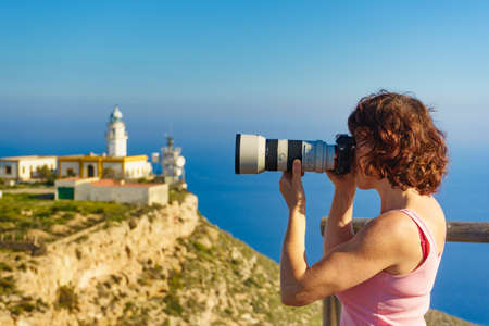 Female tourist with camera taking travel photo from Mesa Roldan lighthouse, Cabo de Gata Nijar Natural Park in Almeria province, Andalusia Spain.