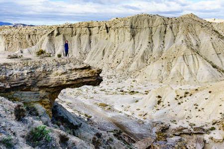 Female tourist enjoying Tabernas desert wild and barren landscape in Almeria, Spain. Movie location set for spaghetti western.