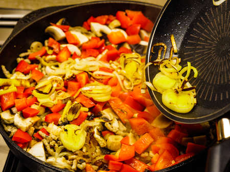 Making delicious dinner food meal. Adding fresh sliced fried onion to hot pan with mixed vegetables. Stock fotó