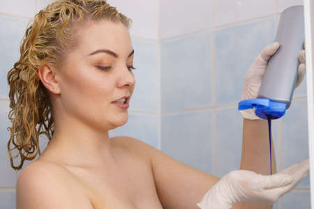 Woman applying coloring shampoo on her hair. Female having purple washing product. Toning blonde color at home. 版權商用圖片