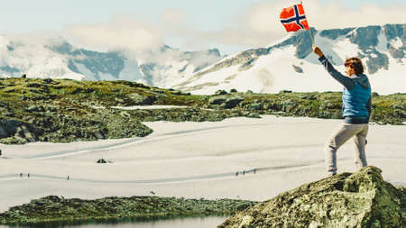 Tourist woman enjoy mountains landscape, holding norwegian flag. National tourist scenic route 55 Sognefjellet, Norway